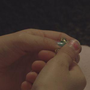 Pikkutytön kädet pitelevät korua