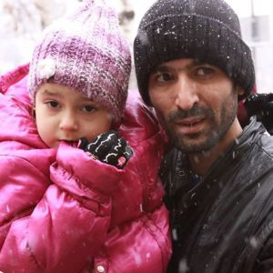 Isänsä menettänyt pieni tyttö setänsä sylissä.