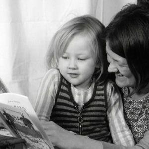 Äiti lukee kirjaa lapsensa kanssa