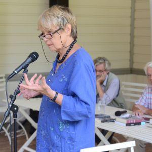 silmälasipäinen nainen puhuu mikrofoniin seisaaltaan