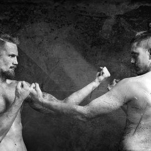 Viiksekkäät miehet vastakkain poseeraavat nyrkit pystyssä ja ilman paitaa.