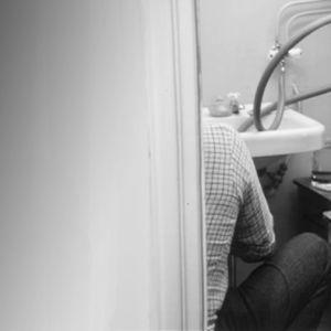 Mies keittää pontikkaa vessassa.