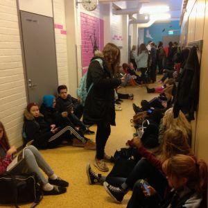 Oppilaat istuvat käytävässä välitunnilla