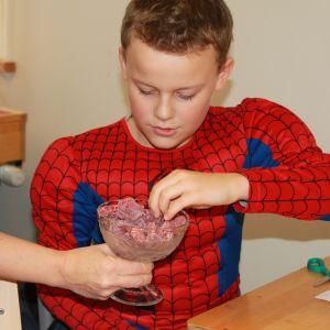 hämähäkkipukuun pukeutunut oppilas ottaa karkkia maljasta