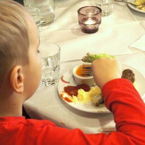 Lapsi syö ravintolassa ruokaa.