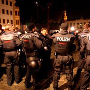 Poliisi valmistautuu äärioikeistolaisen Pegidan mielenosoitukseen pimenevässä illassa Saksan Dresdenissä