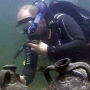 """Vladimir Putin """"löytää"""" merenpohjasta arvokkaita vaaseja. Kuvakaappaus uutisista (2011)"""