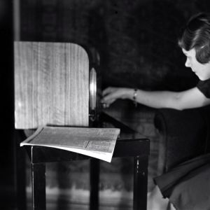Sirkka Miettinen kuuntelee radiota. Radion vieressä sanomalehti. Kuva otettu 1930-luvulla