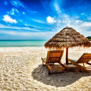 kaksi aurinkotuolia hiekkarannalla