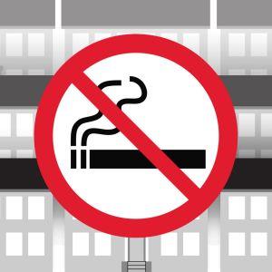 Grafiikka: tupakointi kielletty -merkki, kerrostaloja.