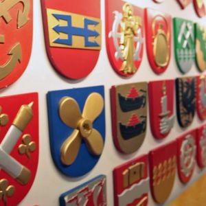Paljon vaakunoita Kuntatalon seinällä Helsingissä.