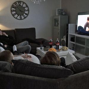 Poikia katselemassa elokuvaa televisiosta kotisohvalla.