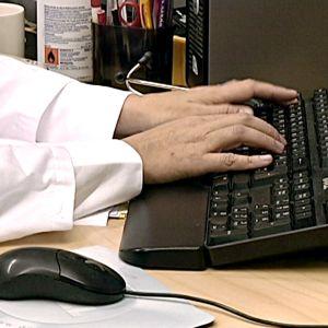 Läkare skriver något på ett tangentbord.