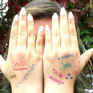 En flicka som håller händerna för ansiktet. På händerna står skrivet olika komplimanger så som du är vacker.