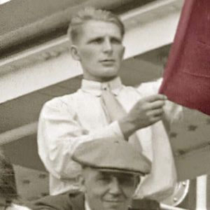 Suomalaissiirtolainen heiluttaa punalippua ja laulaa työläismarssia laivan lähtiessä kohti Amerikkaa (1930-l).