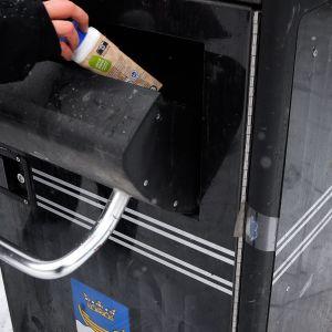 Någon slänger en mjölkkartong i en sopcontainer.