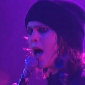 Ville Valo laulaa mikrofoniin lavalla pipo päässä.