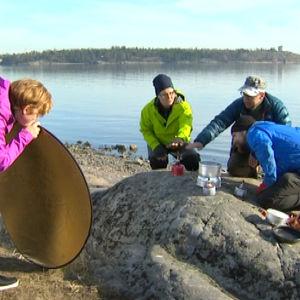 Kolme testaaja ja toimittaja katsovat retkikeittimiä kalliolla