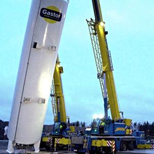 En stor och avlång LNG-tank lyfts på plats med hjälp av två lyftkranar vid Stormossen i Korsholm.
