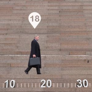 Mies kävelee salkku kädessä grafiikan seassa.