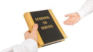 Käsi ojentaa kirjaa toiselle kädelle. Kirjan kannessa lukee: Learning to Survive.