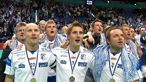 Bild på lagkamrater som sjunger med guldmedalj runt halsen