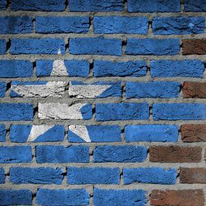 Somailas flagga på en sprucken tegelmur.