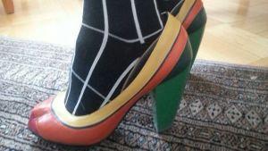 högklackade skor i olika färger på en matta