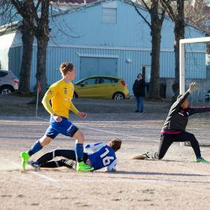 En pojke i blå shorts och gul tröja sparkar mål i fotboll i Hangö. Pojken heter Miska Henriksson.