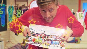 BUU-klubbsledaren Staffan Gräsbeck håller upp pappersjulkalendern 2015.