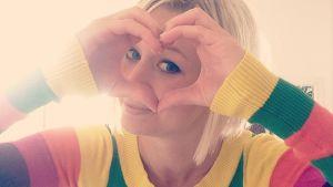 Esther Kazen iklädd en regnsbågsrandig tröja. Formar händerna som ett hjärta.