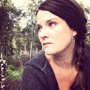 Camilla Forsén-Ström framför blomsteräng och staket