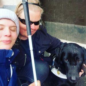 Alina Tomnikov, Johanna Herranen ja Johannan koira tiiviisti lähekkäin ulkona kyykyssä.
