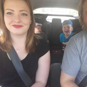 Paret sitetr i en bil, på bakbänken två barn.