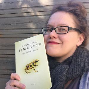Kirjabloggaaja Reeta Törrönen pitää kädessään Veronica Pimenoffin romaania.