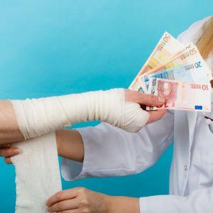 En kvinnlig doktor tar emot pengar för att sköta en patient.