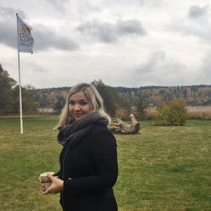 Cindy Viinikka som står ute på en gård, bredvid Gripsholmsskolans flagga.