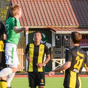 Flera fotbollsspelare tävlar om bollen på en fotbollsplan.