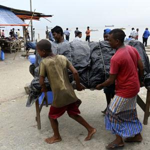 Invånare i Bangladesh flyttar sitt försäljningsstånd undan stormen Mora.