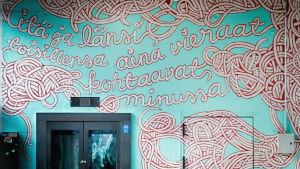 Seinässä katutaideteoksessa kaunikirjoituksella teksti itä ja länsi toisillensa aina vieraat kohtaavat minussa