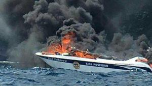Båt brinner, tjock svart rök stiger upp.