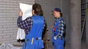 Kaksi rakennusmiestä, joista toinen tutkii rakennuspiirustuksia.