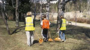 Kolme nuorta puistossa haravien kanssa.