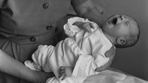 Itkevä vauva kätilön sylissä (1960-luku).