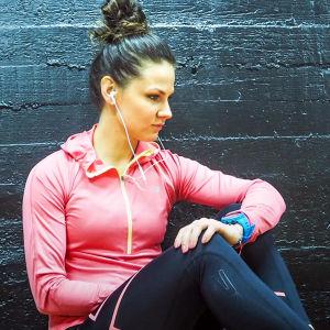 Elina Hovinen istuu lattialla ja nojaa mustaa seinaa vasten.