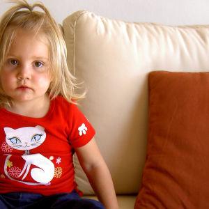 Lapsi istuu sohvalla.