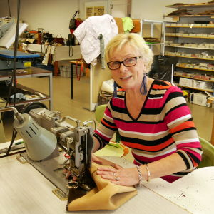 Annikki Koivunen ompelee nahkalaukun mallikappaletta.