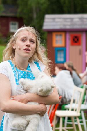 Kvinna håller i ett gosedjur i en scen ur Pedersöre sommarteaters uppsättning av Alice i underlandet.