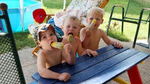 Barn sitter vi parkbord och äter glass