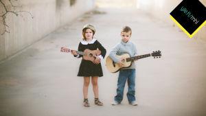 tyttö ja poika soittavat kitaraa